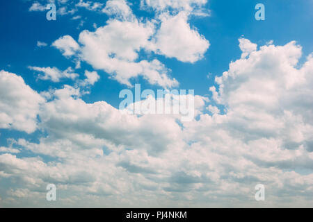 Cumulus white clouds on a blue summer sky background - Stock Photo