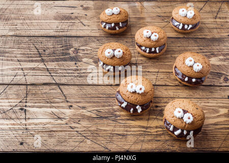 Cookies with chocolate paste in the form of monsters for Halloween. - Stock Photo