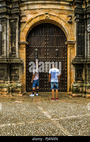 Two men knocking on an old door in Ronda - Stock Photo