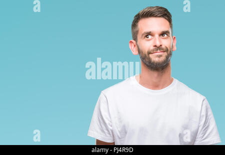 Young handsome man over isolated background smiling looking side and staring away thinking. - Stock Photo
