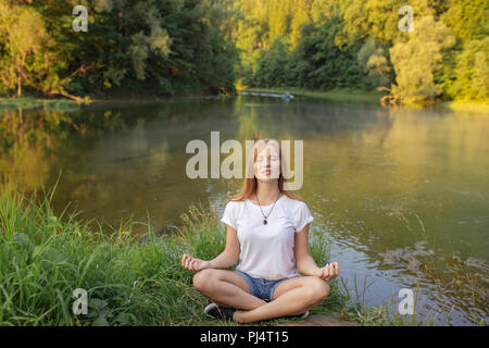 young healthy fit woman practice yoga on the bank of river - Stock Photo