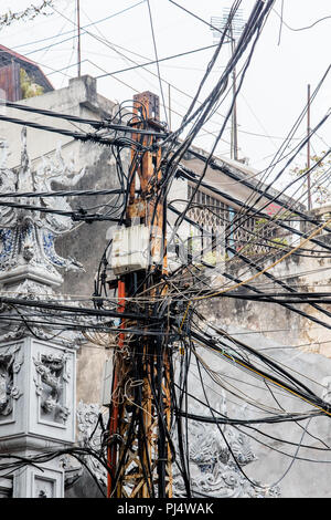 Tangled hub of wires and cables around telephone pole in old town, Hanoi, Vietnam - Stock Photo