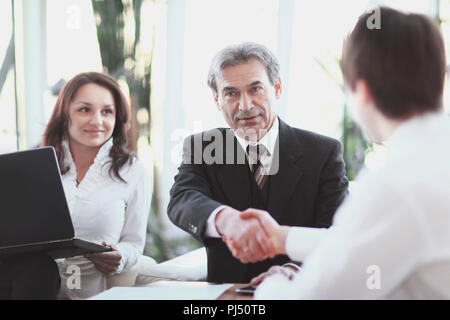 closeup. handshake Manager and client sitting at Desk - Stock Photo