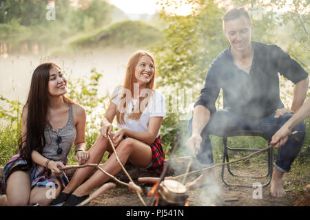 cheerful girls and pleasant boy are cooking on bonfire - Stock Photo