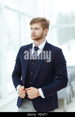 pensive young businessman standing near the office window - Stock Photo