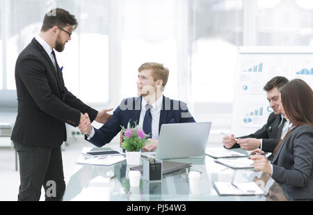 handshake Manager and employee in the workplace - Stock Photo