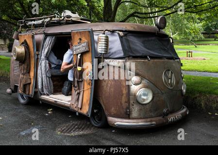 A vintage rat look Volkswagen camper van parked at the roadside. - Stock Photo