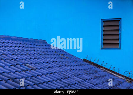 Blue background. House wall, tiled roof painted in various shades of blue color. Village Kampung Biru is popular place to visit for city walking tour. - Stock Photo