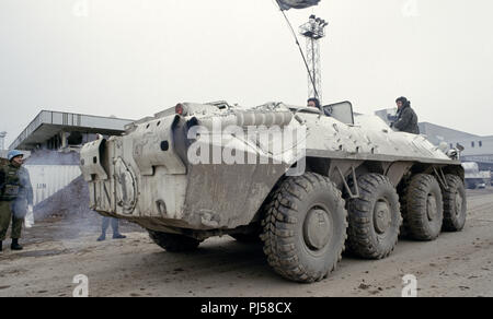 8th March 1993 During the Siege of Sarajevo: a United Nations Ukrainian BTR-80 Armoured Personnel Carrier sputters smoke from its exhausts as it sits parked near the damaged terminal building at Sarajevo Airport. - Stock Photo