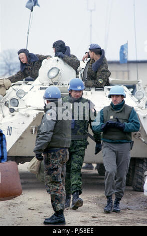8th March 1993 During the Siege of Sarajevo: near the terminal building at Sarajevo Airport, a Norwegian captain talks with a French soldier as they walk away from a parked Ukrainian BTR-80 APC, its crew on board. - Stock Photo