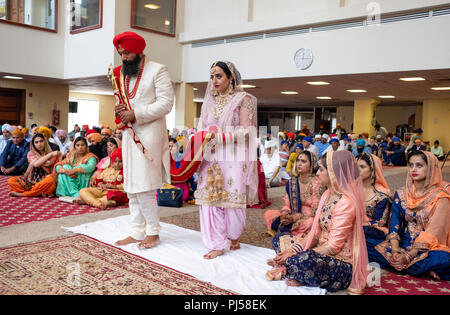 A Sikh bride and groom in a temple during their wedding ceremony. In Queens, New York City - Stock Photo