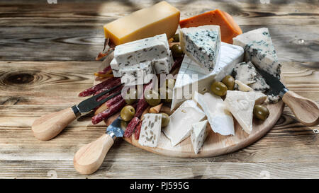 Different sorts of cheese on a wooden board - Stock Photo