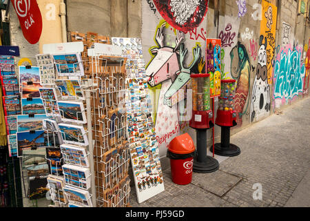 Portugal, Porto, Avenida Dom Afonso Henriques, souvenirs on display by graffiti covered wall - Stock Photo