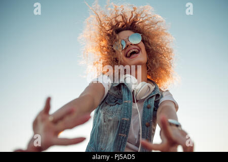 Young stylish woman with very lush hair makes a friendly gesture. Young woman with big headphones. outdoors portrait of a trendy girl - Stock Photo