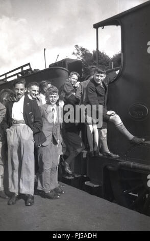 1930s, a group of schoolboys on at a railway platform beside and standing on the side of a Southern railway 733 steam locomotive, England, UK. - Stock Photo