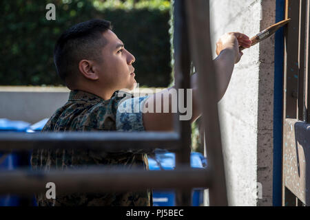 U.S. Marine Corps Staff Sgt. Rubin Tan, a communication strategy and operations chief with Headquarters Regiment, 1st Marine Logistics Group, paints a fence at the Ronald McDonald House during a community service event at Los Angeles Fleet Week, Aug. 30, 2018. Los Angeles Fleet Week provides an opportunity for the Marine Corps and Navy to demonstrate the quality of personnel to the citizens of Los Angeles and surrounding areas. Los Angeles Fleet Week celebrates and honors the nation's sea services, facilitates annual disaster preparedness training between the Navy, Marine Corps, Coast Guard an - Stock Photo