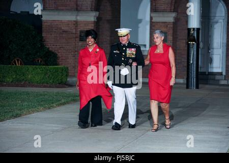 From left, Dr. Betty Moseley Brown, President of the Women Marines Association, Commandant of the Marine Corps Gen. Robert B. Neller, and D'Arcy Neller, walk down Center Walk during an evening parade at Marine Barracks Washington, Washington D.C., Aug. 31, 2018. Gen. Neller hosted the parade and the guest of honor was Dr. Betty Moseley Brown.(U.S. Marine Corps photo by Sgt. Olivia G. Ortiz) - Stock Photo