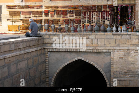 Old man in a market road in Bukhara Uzbekistan with carpet and vases - Stock Photo