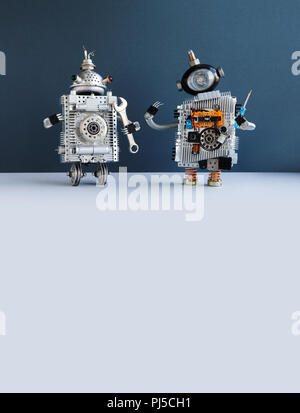 Two funny mechanic handyman robots with screw driver and hand wrench on blue gray background. copy space. - Stock Photo