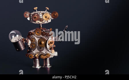 Robot handyman with screw driver and light bulb. Fixing maintenance concept. Creative design mechanic toy character. Dark blue background. Copy space. - Stock Photo
