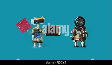 Robotics 4.0 industrial revolution concept. Two robots with circuit board memory card and light bulb on virid color background. Isolated - Stock Photo
