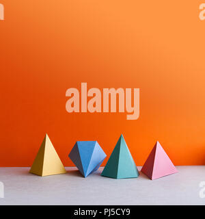 Platonic solid geometric figures. Three-dimensional pyramid rectangular triangle objects on orange gray background. Yellow blue red green colored tetrahedron abstract shapes objects. copy space. - Stock Photo