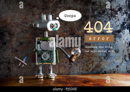 404 error page not found. Robot handyman with screw driver and light bulb on aged metalic background. Text message Something went wrong but we are working on it - Stock Photo