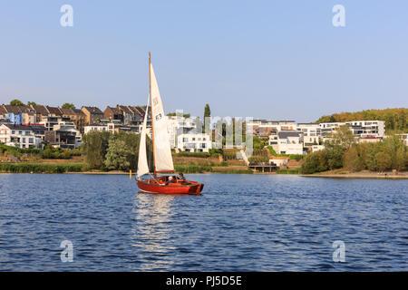 Sailboat on Phoenix See, Phoenixsee, a popular urban lake in Horde, Dortmund, with modern residential architecture, Ruhr area, Nordrhein-Westfalen, Ge - Stock Photo