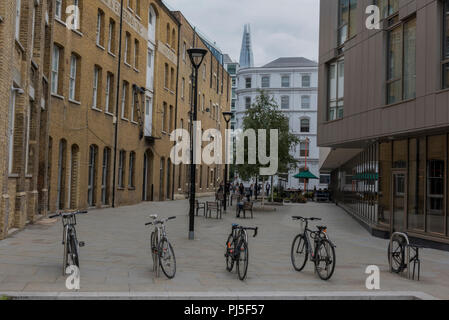 bicycles parked on a stand in a small quiet paved pedestrian square in central London with the shard office building in the background. - Stock Photo