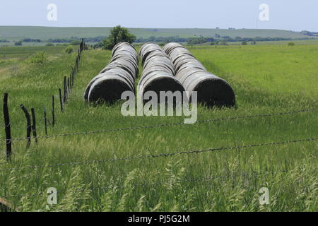 Kansas Hay Bales with a barb wire fence and green grass. - Stock Photo