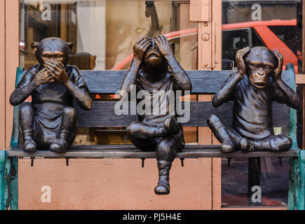 Bronze Sculpture Of Three Wise Monkeys Sitting On A Bench Taken In Chinatown San Francisco - Stock Photo