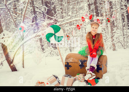 a little red-haired girl with long hair in a lush skirt and a green cloak with lace, in the costume of dwarf assistant Santa Claus in the winter forest with huge candy, a chest of gifts collects in a basket Christmas balls - Stock Photo