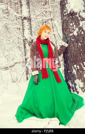 fiery red-haired woman in a ball green dress with a red leather belt in the costume of dwarf assistant Santa Claus in the winter forest with huge cand - Stock Photo