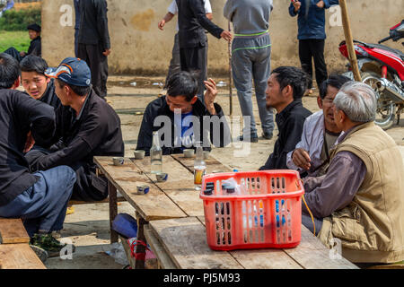 Ha Giang, Vietnam - March 18, 2018: Vietnamese men drinking together at Dong Van sunday market - Stock Photo