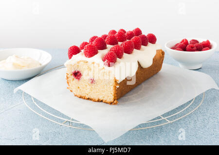 Closeup of a homemade raspberry loaf cake on parchment paper and cooling rack. Bowls filled with fresh raspberries and frosting in the background. - Stock Photo