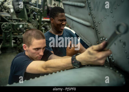 """180824-N-AT135-0008  SOUTH CHINA SEA (Aug. 24, 2018) – Aviation Structural Mechanics 3rd Class Daryl Beres and Demario Murraychambers perform maintenance on an MH-60S Sea Hawk helicopter, attached to the """"Blackjacks"""" of Helicopter Sea Combat Squadron (HSC) 21, in the hangar bay of Wasp-class amphibious assault ship USS Essex (LHD 2) during a regularly scheduled deployment of the Essex Amphibious Ready Group (ARG) and 13th Marine Expeditionary Unit (MEU). The Essex ARG/13th MEU is a capable and lethal Navy-Marine Corps team deployed to the 7th fleet area of operations to support regional stabil - Stock Photo"""
