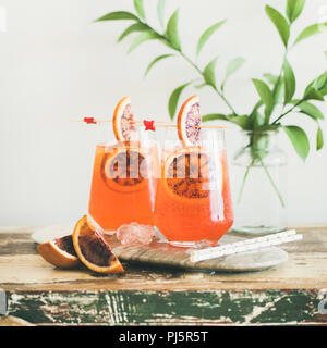 Two glasses of Italian Aperol Spritz alcohol cocktail with ice and blood orange slices on wooden table, selective focus, copy space, square crop. Summ - Stock Photo