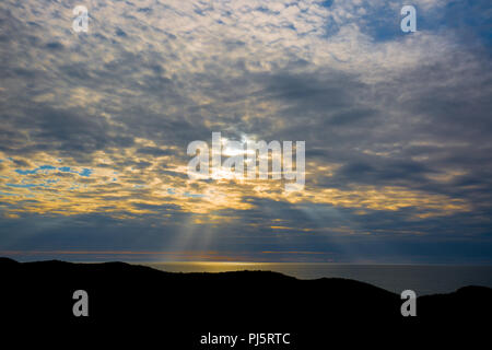 Evening light, looking out to sea from silhouetted headland last rays of sun shine down through broken cloud lighting up ocean. Sun sets over  horizon - Stock Photo