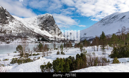 Snow covered mountains above a frozen lake in Folkestad Norway - Stock Photo