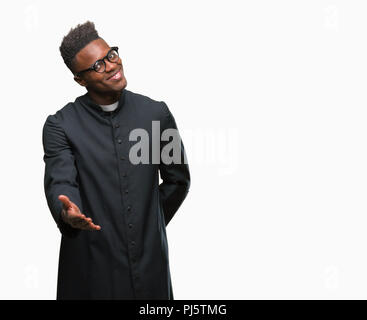 Young african american priest man over isolated background smiling friendly offering handshake as greeting and welcoming. Successful business. - Stock Photo