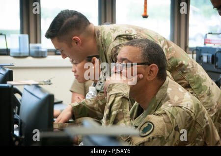 Hawaii National Guard service members monitor post Hurricane Lane activities at the Task Force Hawaii (TF Hawaii) Joint Operations Center in Keaukaha Military Reserve, Hilo, Hawaii, August 27, 2018. TF Hawaii is an extension of the Joint Task Force 5-0 military organization, based in Honolulu, which provides support to state and local disaster response efforts to both the on-going Kilauea Volcano eruptions and Hurricane Lane. (U.S. Air National Guard photo by Senior Airman Robert Cabuco) - Stock Photo