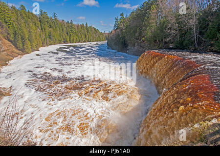 Rushing Waters over a Flooded Upper Tahquamenon Falls in Tahquamenon Falls State Park in Upper Michigan - Stock Photo