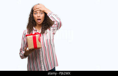 Young hispanic woman in love holding present stressed with hand on head, shocked with shame and surprise face, angry and frustrated. Fear and upset fo - Stock Photo