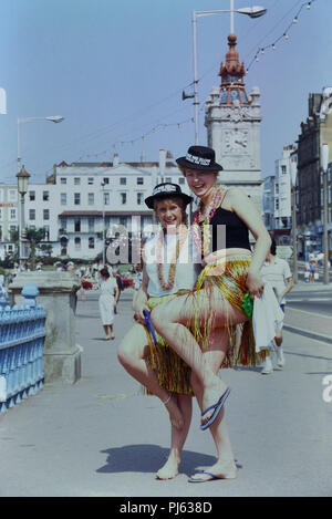 Two young women in fancy dress wearing Kiss me slow squeeze me tight hats, Margate, Kent, England, UK. Circa 1980's - Stock Photo