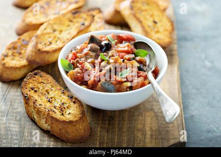 Eggplant caponata crostini or bruschetta on garlic bread - Stock Photo