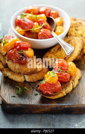Roasted tomatoes bruschetta with thyme on garlic bread - Stock Photo
