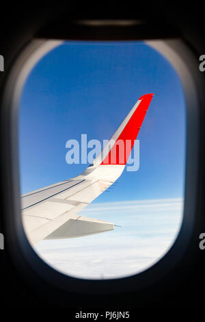 Airliner wing as seen through window of flying airplane - Stock Photo