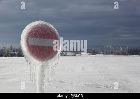 Frozen rain on the red traffic sign in the gray cold morning - Stock Photo