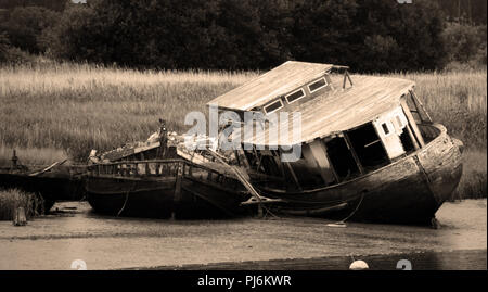 An abandoned and decaying houseboat moored on the mud at low tide on the River Exe near Topsham, Devon, England - Stock Photo