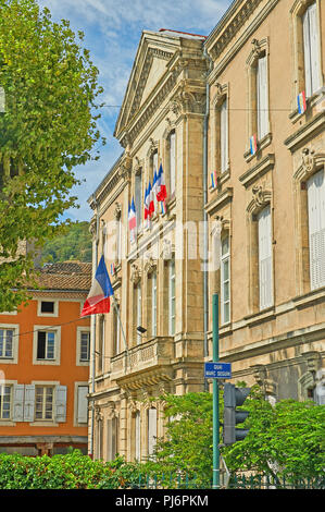 Tournon sur Rhone, Ardeche department, Rhone Alps, France and an ornate stone building with French tricoloure flags flying. - Stock Photo